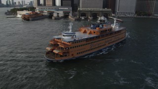 AX88_162 - 4K stock footage aerial video of orbiting the Staten Island Ferry leaving the Lower Manhattan terminal, New York