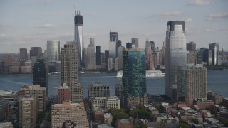 AX88_173 - 4K stock footage aerial video of cruise ship passing Lower Manhattan skyscrapers, seen from Downtown Jersey City, New Jersey