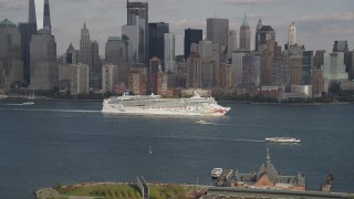 AX88_175 - 4K stock footage aerial video of a cruise ship sailing past Lower Manhattan skyline, New York, New York