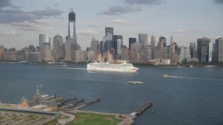 AX88_176 - 4K stock footage aerial video of tracking a cruise ship sailing by skyline of Lower Manhattan, New York, New York