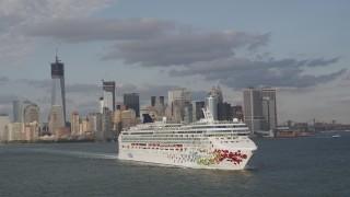 AX88_188 - 4K stock footage aerial video of tracking cruise ship sailing New York Harbor, revealing Lower Manhattan skyline, New York