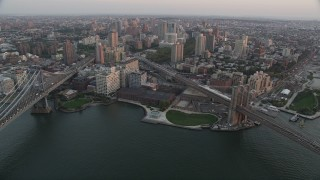 AX89_010 - 4K stock footage aerial video Approaching Brooklyn, Manhattan and Brooklyn Bridges, New York, sunset