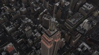 AX89_050 - 4K stock footage aerial video of a Bird's eye view over Empire State Building, Midtown Manhattan, New York, twilight