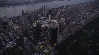 AX89_086 - 4K stock footage aerial video Flying by skyscrapers, Columbus Circle, Upper West Side, New York, twilight