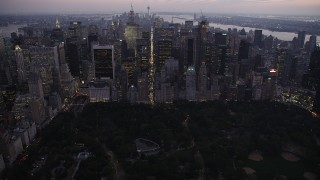 AX89_091 - 4K stock footage aerial video Approaching Central Park, revealing Midtown Manhattan, New York, twilight