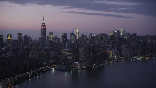 AX89_114 - 4K stock footage aerial video Flying by Midtown Manhattan, seen from East River, New York, New York, twilight
