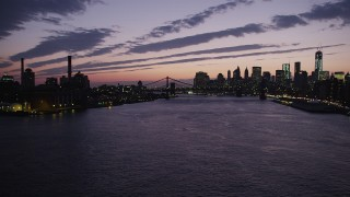 AX89_126 - 4K stock footage aerial video Flying by Manhattan Bridge, Lower Manhattan skyline, New York, twilight