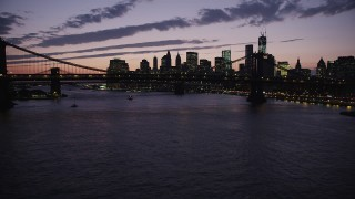 AX89_127 - 4K stock footage aerial video Flying by Manhattan Bridge, Lower Manhattan skyline, New York, twilight