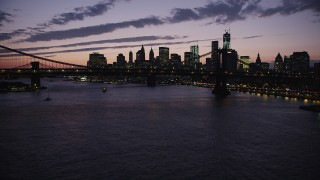AX89_128 - 4K stock footage aerial video Approaching Manhattan Bridge, Lower Manhattan skyline, New York, twilight