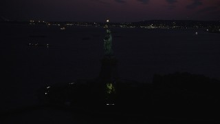 AX89_137 - 4K stock footage aerial video Flying by Statue of Liberty, Liberty Island, New York, New York, twilight