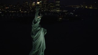 AX89_143 - 4K stock footage aerial video Flying by Statue of Liberty, revealing Lower Manhattan, New York, night