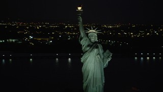 AX89_148 - 4K stock footage aerial video Flying by Statue of Liberty, New York Harbor, New York, New York, night