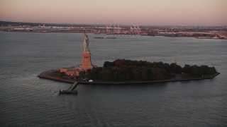 AX90_013 - 4K stock footage aerial video Flying by Statue of Liberty, Liberty Island, New York, New York, sunrise