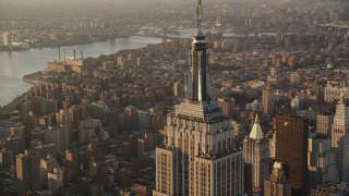 AX90_061 - Aerial stock footage of Flying by Empire State Building, Midtown Manhattan, New York, sunrise