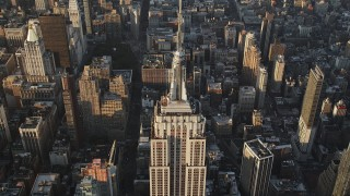 AX90_088 - 4K stock footage aerial video Approaching top of Empire State Building, Midtown Manhattan, New York, sunrise