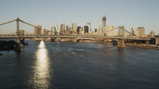 AX90_100 - 4K stock footage aerial video of Manhattan Bridge, Lower Manhattan, reveal Brooklyn Bridge, New York, sunrise
