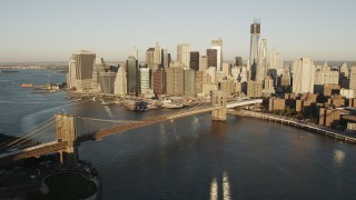 AX90_101 - 4K stock footage aerial video Flying by Brooklyn Bridge, Lower Manhattan skyline, New York, New York, sunrise