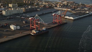 AX90_109 - 4K stock footage aerial video Approaching cargo cranes, Brooklyn Cruise Terminal, Brooklyn, New York, sunrise