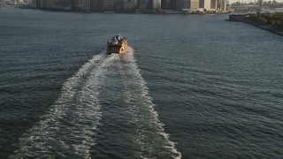 AX90_130 - 4K stock footage aerial video Flying by Staten Island Ferry, tilt up to Lower Manhattan, New York, sunrise