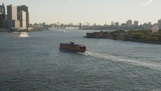 AX90_131 - 4K stock footage aerial video Tracking the Staten Island Ferry near Lower Manhattan, New York, sunrise