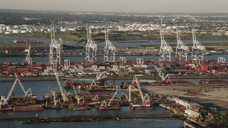 AX90_154 - 4K stock footage aerial video Approaching cargo cranes, containers ,Port Jersey, New Jersey, sunrise