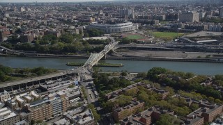 AX91_017 - 4K stock footage aerial video tilt from Harlem apartment buildings, reveal Macombs Dam Bridge and Yankee Stadium in The Bronx, New York