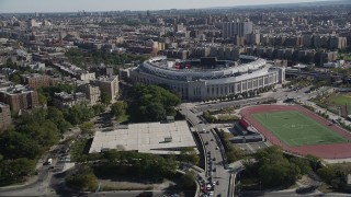 AX91_018 - 4K stock footage aerial video tilt from Macombs Dam Bridge, reveal Yankee Stadium, The Bronx, New York