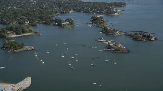 AX91_032 - 4K stock footage aerial video of flying by sailboats and oceanfront mansion on a tiny island, New Rochelle, New York
