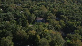 AX91_086 - 4K stock footage aerial video of flying over mansions partially hidden by forest in Darien, Connecticut