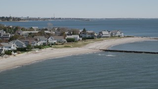 AX91_116 - 4K stock footage aerial video of flying by a beach, breakwaters, and beachfront homes in Fairfield, Connecticut