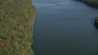 AX91_142 - 4K stock footage aerial video pan from lake to forest with fall foliage, Lake Saltonstall, Connecticut