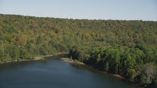 AX91_147 - 4K stock footage aerial video of approaching forest on the shore of the lake in autumn, Lake Saltonstall, Connecticut