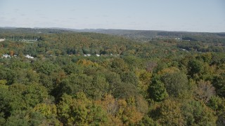 AX91_148 - 4K stock footage aerial video of flying over forest, revealing town in autumn, East Haven, Connecticut