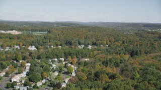 AX91_149 - 4K stock footage aerial video fly over forest, pan to suburban neighborhood in autumn, East Haven, Connecticut