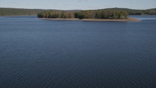 AX91_158 - 4K stock footage aerial video tilt from water, revealing small island in autumn, Lake Gallard, Connecticut