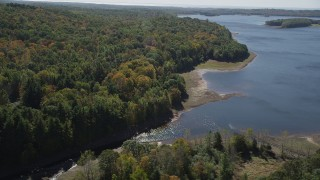 AX91_166 - 4K stock footage aerial video of flying by lush forest on the shore in autumn, Lake Gallard, Connecticut