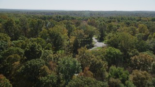 AX91_170 - 4K stock footage aerial video of flying over lush forest, revealing homes in autumn, Guilford, Connecticut