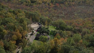 AX91_171 - 4K stock footage aerial video of flying over forest, revealing homes in autumn, Guilford, Connecticut