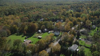 AX91_173 - 4K stock footage aerial video of flying over forest and suburban homes, autumn, Guilford, Connecticut