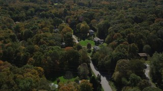 AX91_178 - 4K stock footage aerial video of flying over forest, road and homes in autumn, Guilford, Connecticut