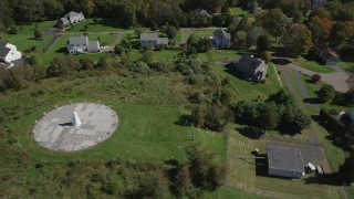 AX91_180 - 4K stock footage aerial video of flying over forest, and by sundial and houses in autumn, Guilford, Connecticut