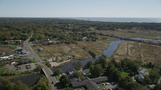 AX91_188 - 4K stock footage aerial video of flying over a river and approaching rural homes in autumn, Guilford, Connecticut