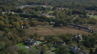 AX91_189 - 4K stock footage aerial video of tracking a passenger train through forests and past businesses in autumn, Guilford, Connecticut