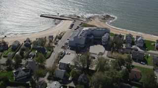 AX91_191 - 4K stock footage aerial video of flying by a beachfront hotel and homes in Madison, Connecticut