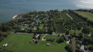 AX91_197 - 4K stock footage aerial video of approaching waterfront homes and vineyard in Southold, New York