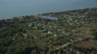 AX91_202 - 4K stock footage aerial video of flying by upscale homes in a coastal neighborhood, Southold, New York