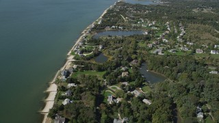 AX91_203 - 4K stock footage aerial video of flying by upscale homes in a coastal neighborhood, Southold, New York