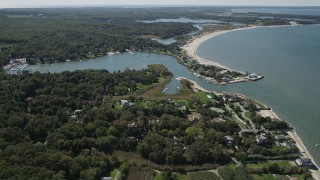 AX91_205 - 4K stock footage aerial video approach Wooley Pond, tilt to upscale beachfront homes, Southampton, New York