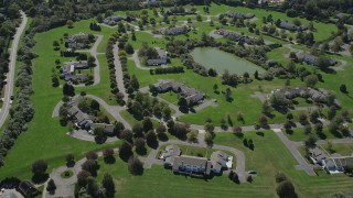AX91_209 - 4K stock footage aerial video of flying over upscale homes near a small pond in Southampton, New York