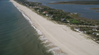 AX91_217 - 4K stock footage aerial video of flying past a beach, tilt to reveal beachfront mansions, Southampton, New York
